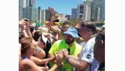 Sem máscara, Bolsonaro provoca aglomeração em praia de SP, abraça banhistas e pega crianças no colo