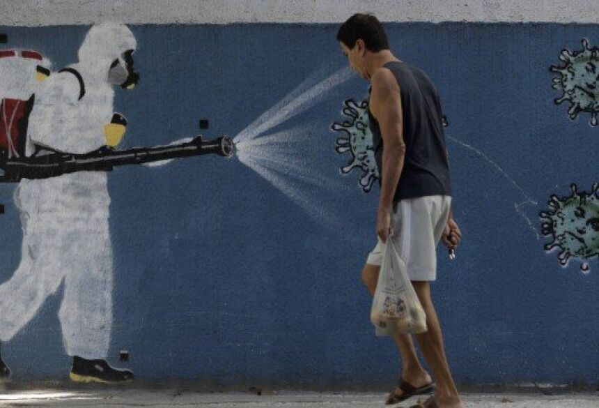 Homem caminha sem máscara em frente a grafite no Bairro do Estácio, Zona Norte do Rio de Janeiro Foto: Luiza Moraes