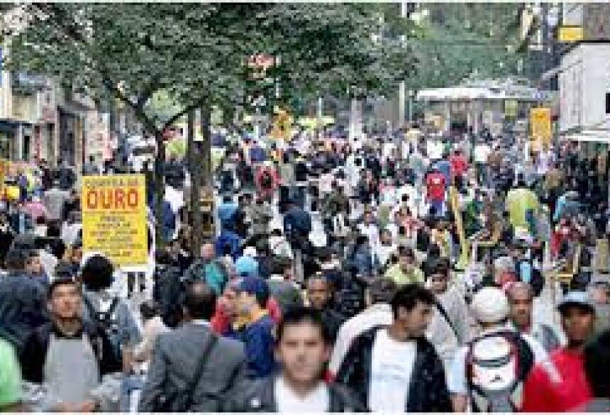 Pessoas caminham em rua comercial popular de São Paulo em meio à pandemia de Covid-19