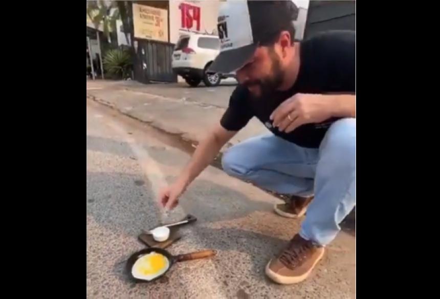 O empresário coloca o ovo, que imediatamente começa a fritar.