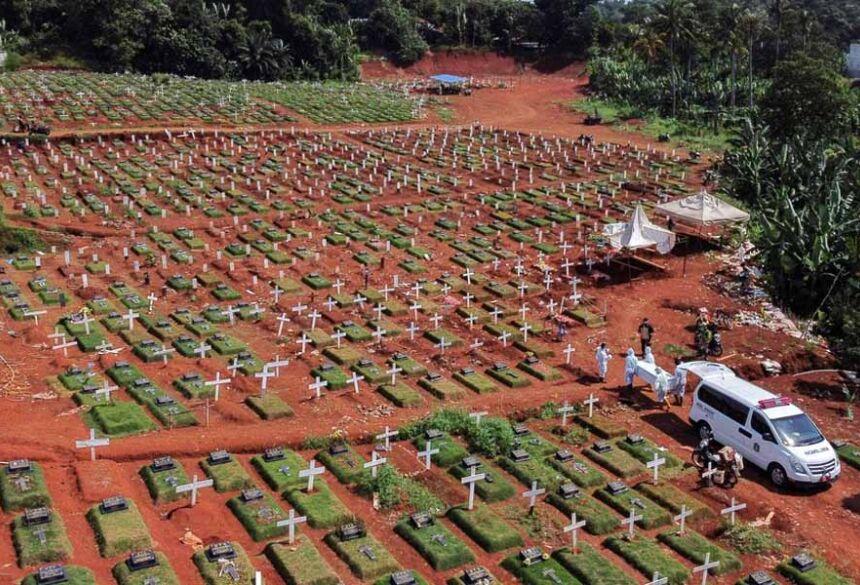 Vista aérea de um cemitério em Jacarta, na Indonésia, mostra coveiros com roupas de proteção carregar um caixão com uma vítima de Covid durante a pandemia do novo coronavírus  Foto: Willy Kurniawan/Reuters