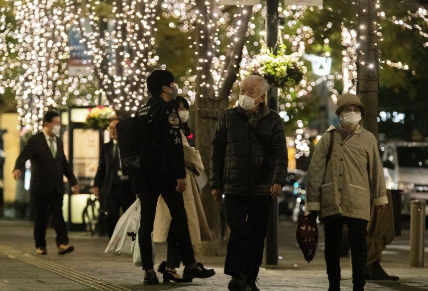 Pedestres caminham de máscara em rua de Tóquio durante a pandemia do novo coronavírus (Covid-19) no Japão