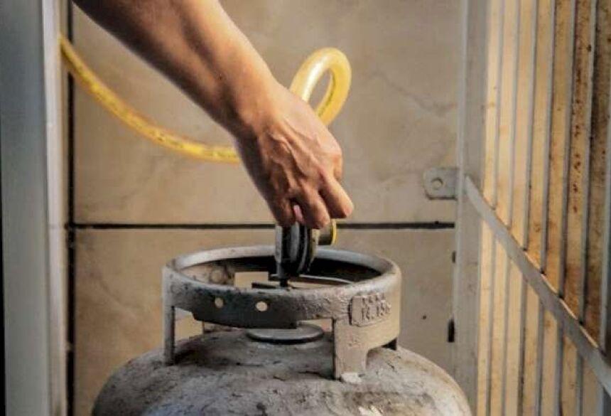 Dona de casa abrindo o registro de um botijão de gás de cozinha. (Foto: Marcos Maluf)