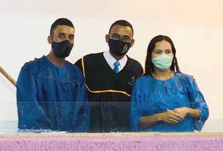 Pastor Joelson entre duas pessoas que foram batizadas