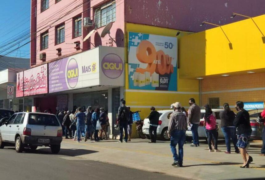 Pessoas em fila que dobra esquina para atendimento no centro de Dourados
