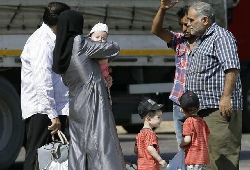 Refugiados sírios passam pela fronteira e entram em território turco para fugir da guerra Foto: AP