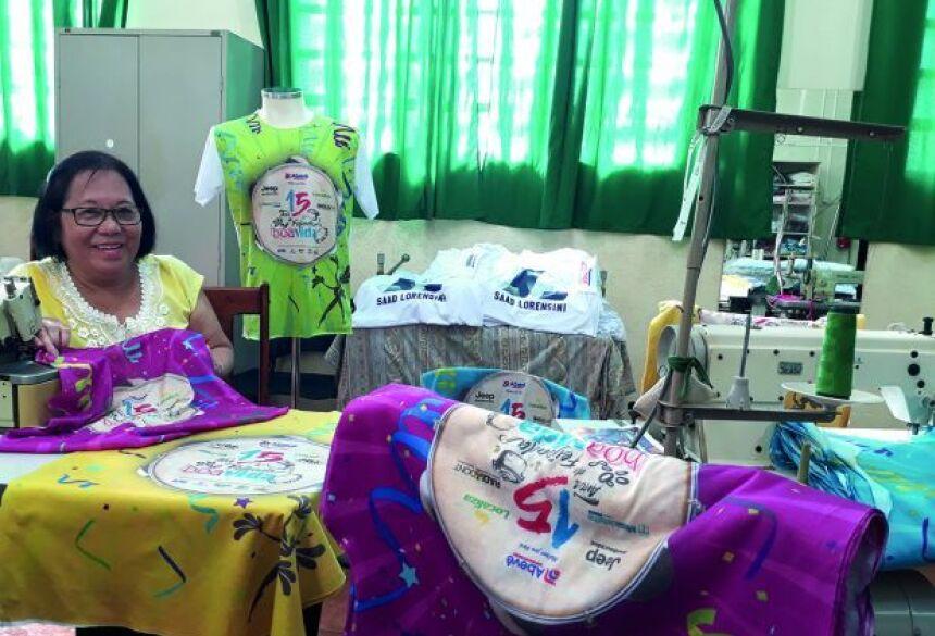 Costureira do Ceia, Sueli Miyai, posa com camisetas que estão em fase de confecção, nas cores verde, pink, azul, roxo e amarelo