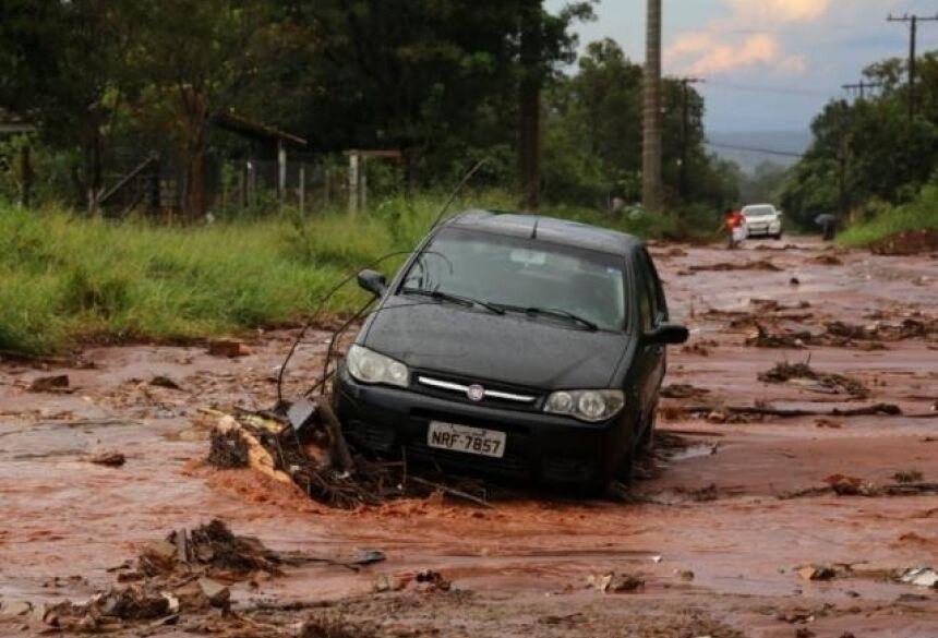 Fiat Pálio atolado em rua do Jardim Noroeste; enxurrada chegou a encobrir veículo (Foto: Paulo Francis)
