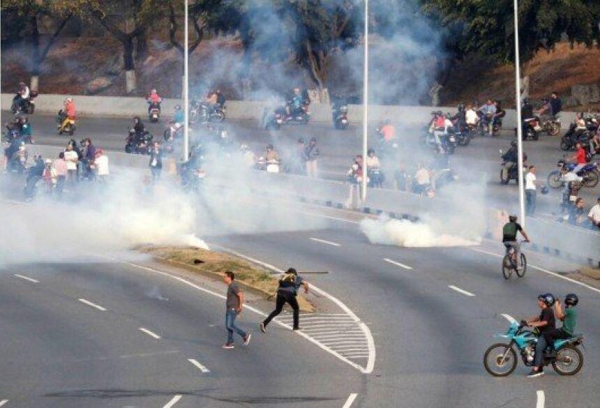Bombas de gás lacrimogêneo são jogadas contra manifestantes na base militar de La Carlota, na Venezuela Foto: CARLOS GARCIA RAWLINS / REUTERS