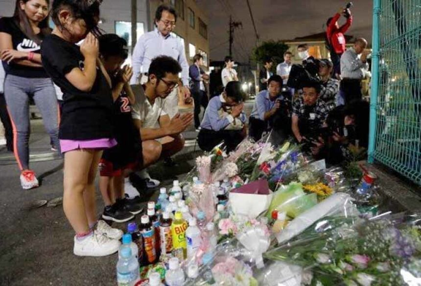 Pessoas rezam após deixarem flores perto do ponto de ônibus onde crianças foram esfaqueadas em Kawasaki, no Japão Foto: ISSEI KATO / REUTERS