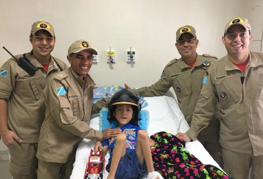 O garoto ficou muito feliz com a visita surpresa e com o capacete de incêndio na cabeça, posou sorridente para as fotos.