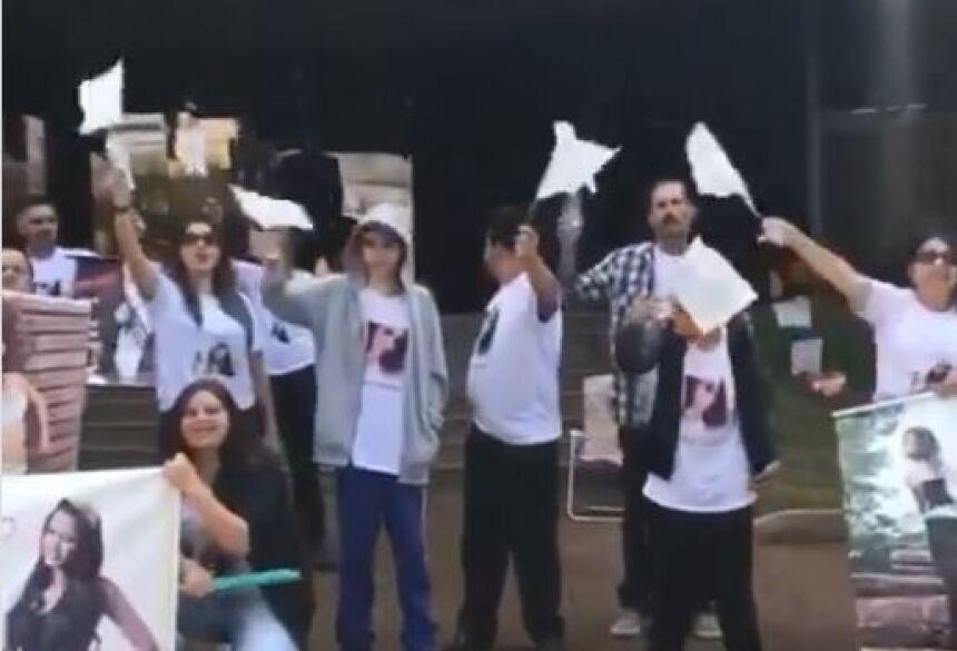 manifestação, com camisetas com a foto da modelo e cartazes