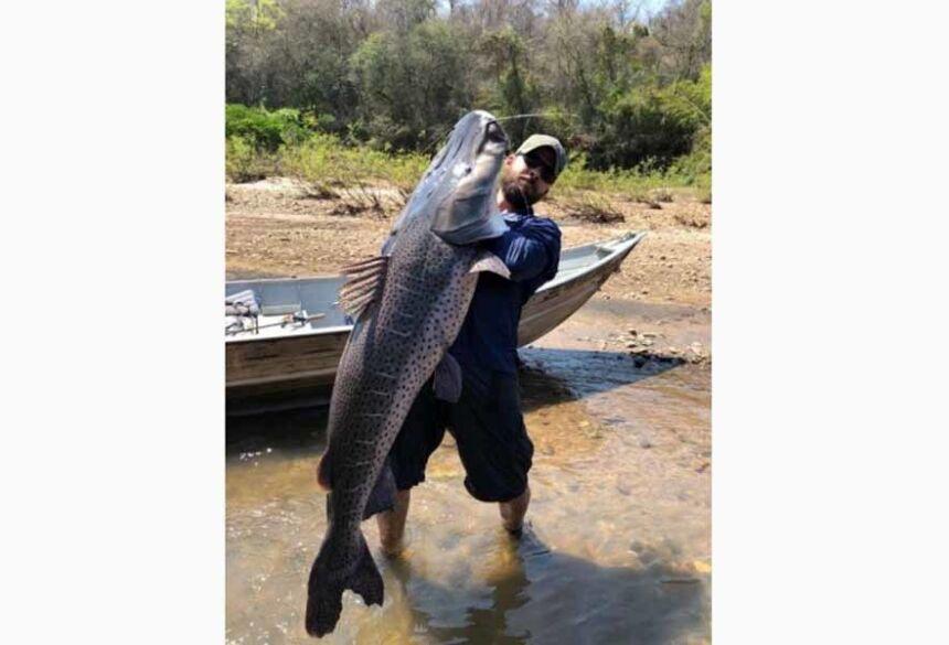 Pescador posando para foto com o peixão. (Foto: O Pantaneiro)