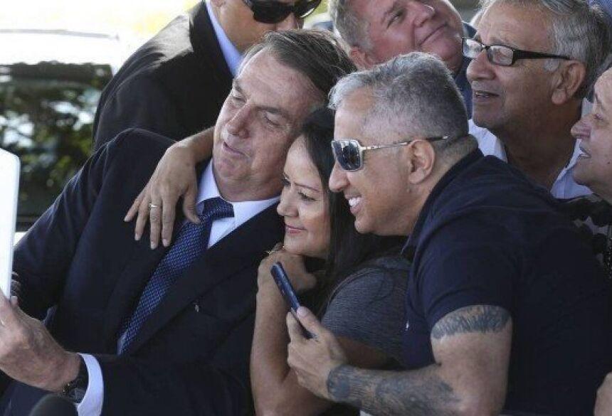 O presidente Jair Bolsonaro, cumprimenta populares no Palácio da Alvorada. Foto: Antonio Cruz/ Agência Brasil