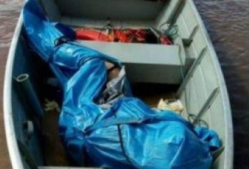 O corpo da vítima em um barco, logo depois de ser tirado do rio por militares