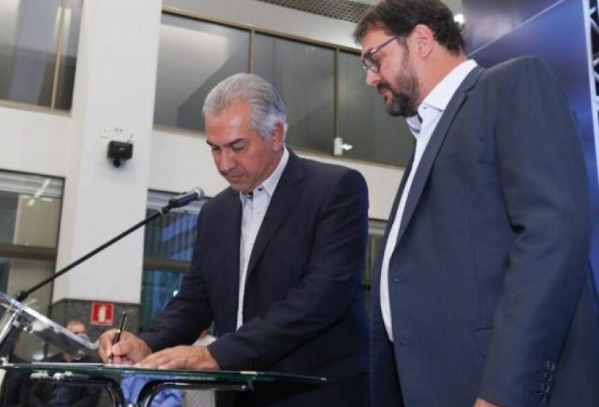 Governador Reinaldo Azambuja (PSDB) assinando termo de adesão ao lado de Sérgio Longen (Foto: Marcos Maluf)