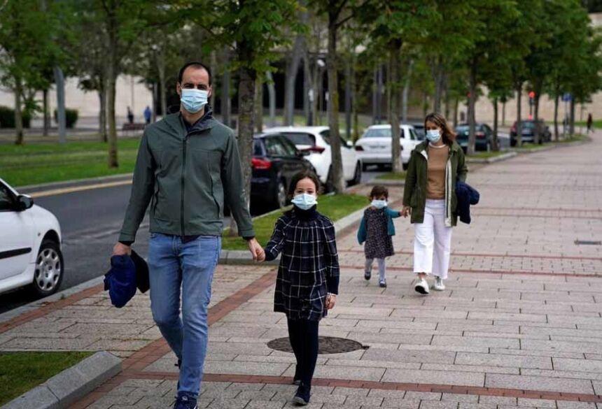 Uma família que usa máscaras protetoras dá um passeio depois que as restrições foram parcialmente levantadas para crianças pela primeira vez em seis semanas, durante o surto da doença por coronavírus em Bilbao, norte da Espanha, neste domingo (26) — Foto: