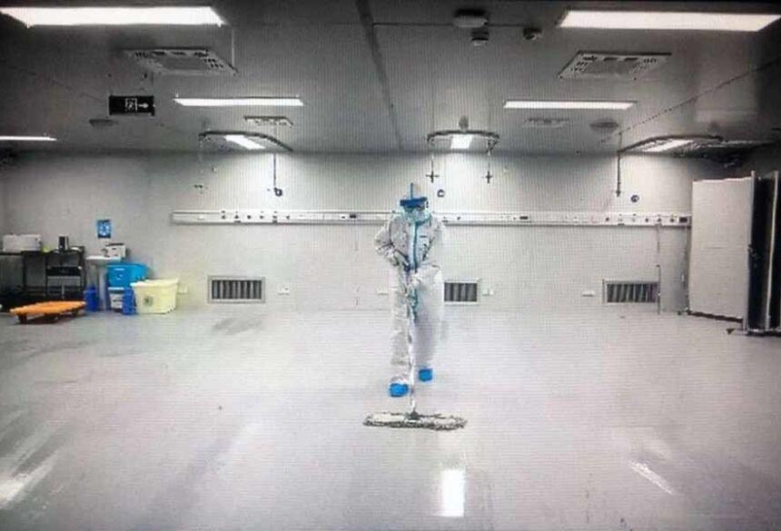 Funcionário limpa o chão de ala de hospital em Wuhan que recebeu pacientes com Covid-19: concentração elevada do vírus em banheiros e em áreas onde médicos tiravam trajes de proteção (foto: AFP)