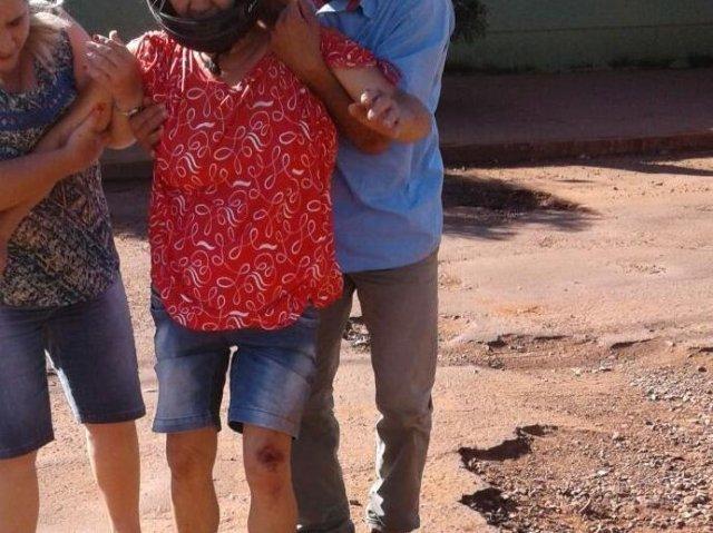 Dona de casa é amparada por moradores após cair de moto em buraco (Foto: Direto das Ruas)