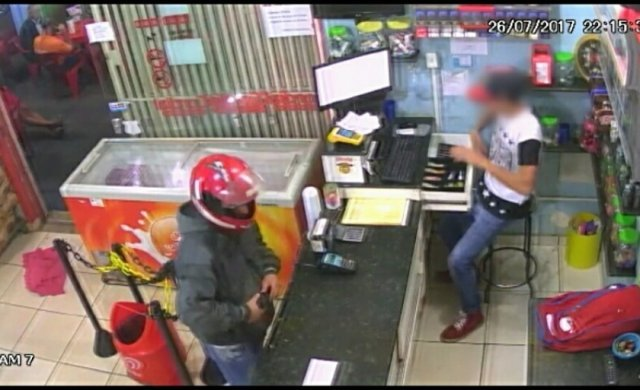 Nas imagens é possível ver os clientes ao fundo e o bandido rende funcionário. (Foto: JP News/ Divulgação)