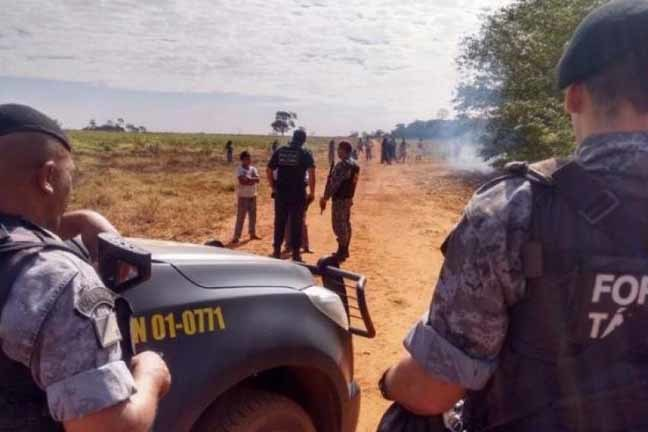 Policiais e homens da Força Nacional conversam com índios em frente à fazenda, na segunda-feira