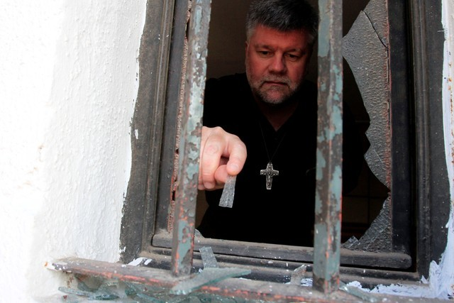 Homem remove cacos de vidro de janela de igreja atacada em Santiago do Chile, poucos dias antes da visita do papa ao país (Foto: Christian Iglesias/Reuters)